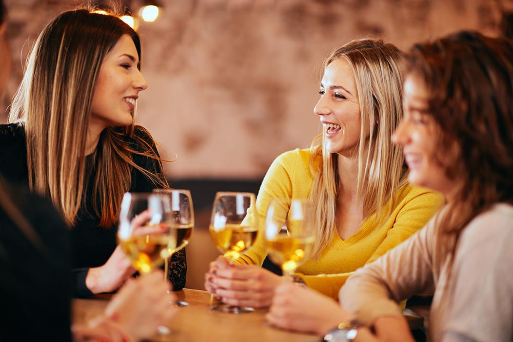 Kvinnor som sitter i en bar och pratar och dricker vin