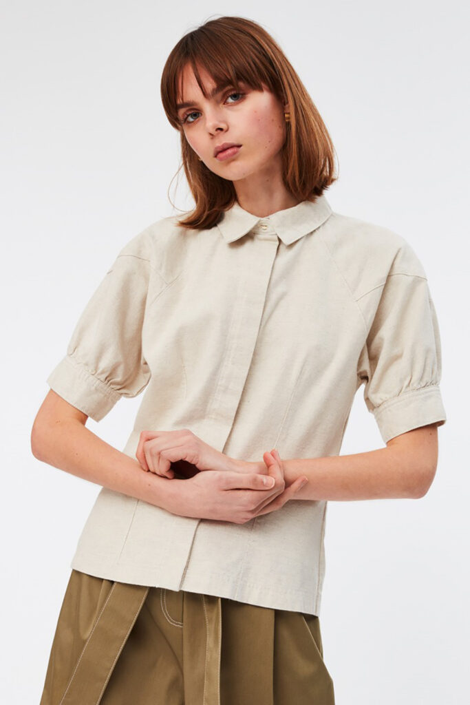 Bild till hållbart mode. Kvinna bär en beige blus och brun kjol. Hon har kort hår och står med lätt korsade armar