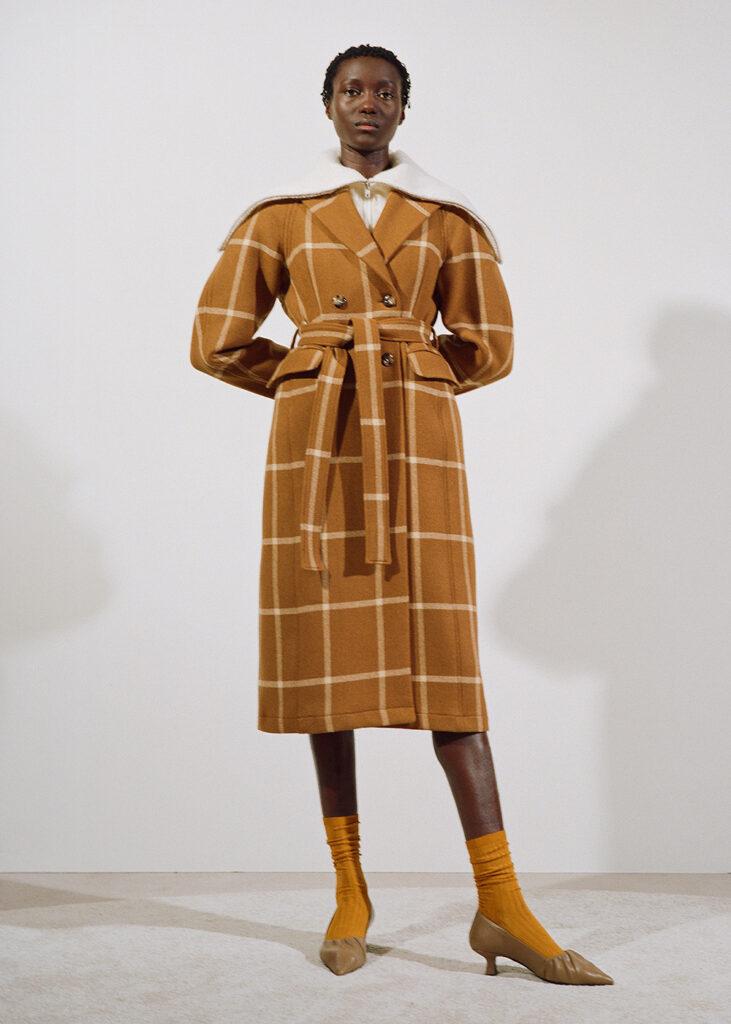 Modell från Stockholm fashion week. Honbär kläder från Rodebjer. Lång Kavaj och låga klackskor i färgen mörkorange.