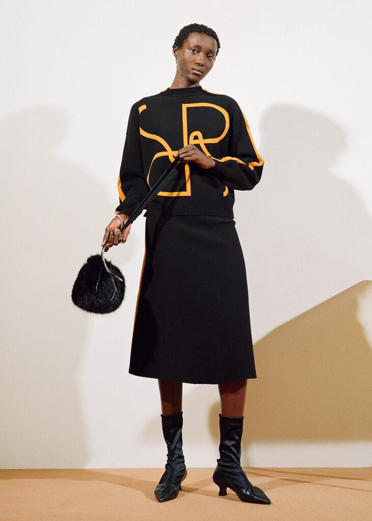 Modell från Stockholm fashion week. Hon bär kläder från Rodebjer. Fluffig väska, mönstrad tröja i svart och orange, en längre kjol och låga klackar.