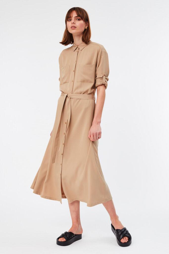Bild till hållbart mode. EN kvinna som har på sig en beige långklänning och svarta sandaler.