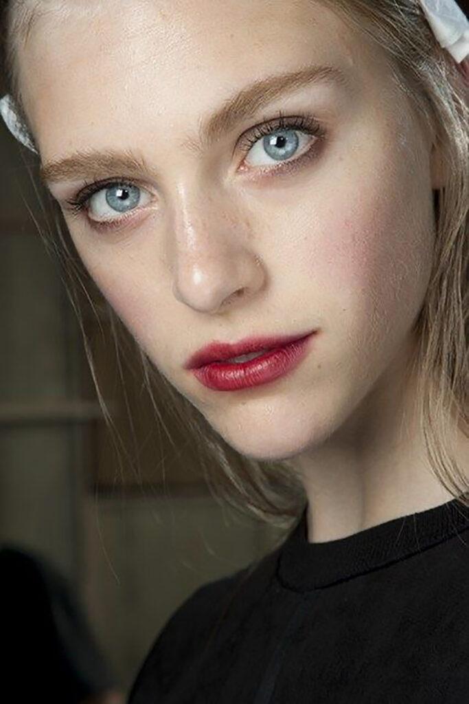 Närbild på en tjejs ansikte med bäriga läppar i röd ton