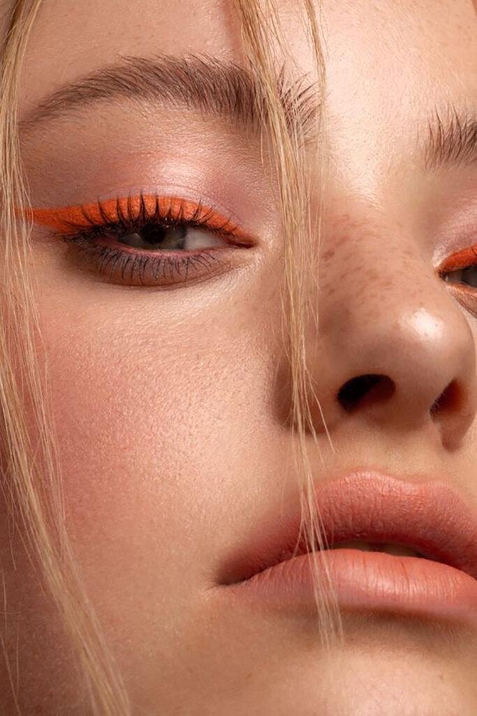Närbild på en tjejs orangea eyeliner
