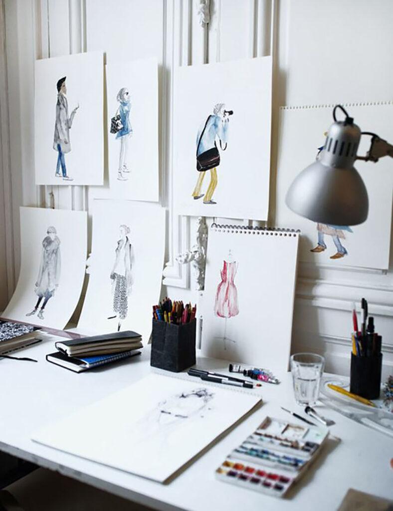 Ett skrivbord med ett block på och skisser av kläder på väggen
