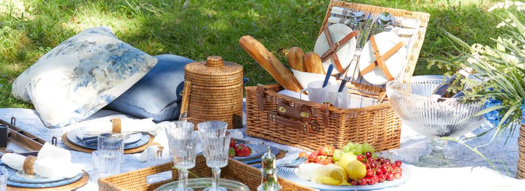 Picknick på en filt. Picknickkorg, mat och glas syns.