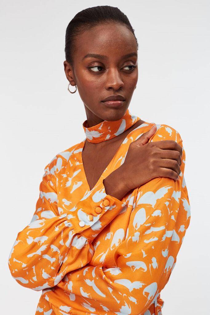 Bild till hållbart mode. Närbild på en kvinna i mönstrad orange blus. Hon har kortklippt hår och håller ena handen över axeln.
